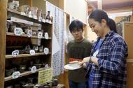 制作例の陶器を見てイメージを膨らます原田さんと多聞さん